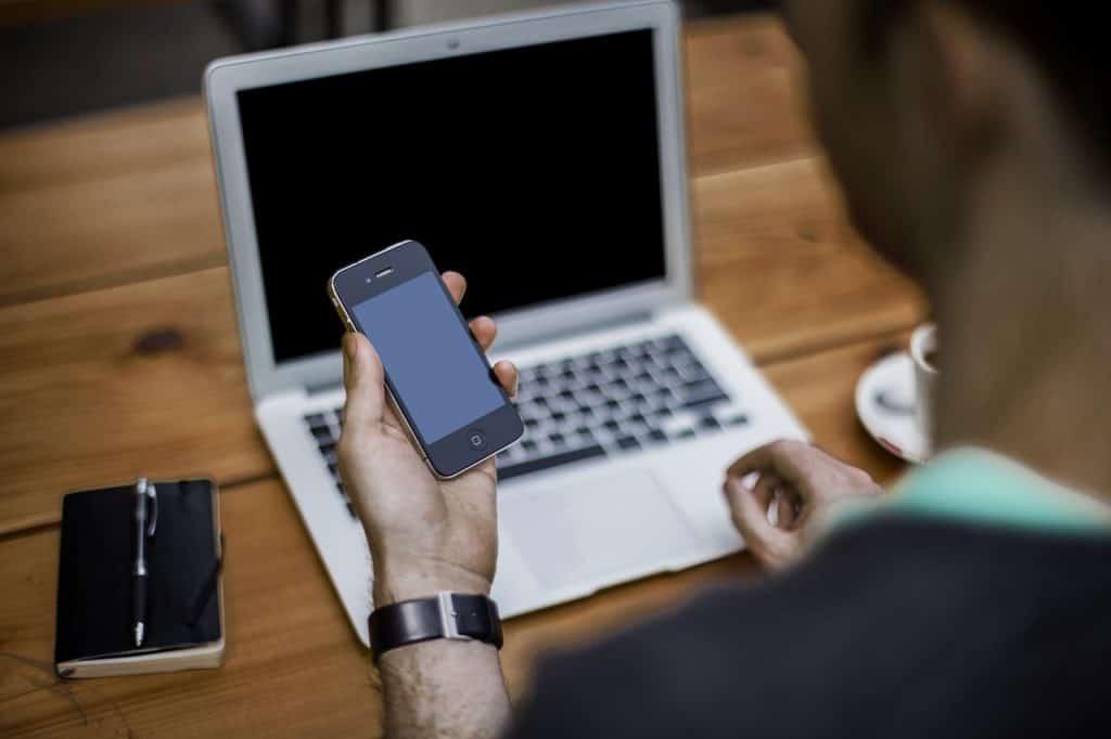אדם מחזיק אייפון מול מחשב
